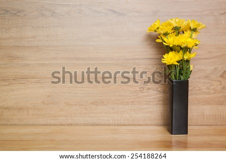 yellow flower Chrysanthemum in vase on wood background