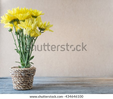 Yellow flower in vase made from bamboo on wooden table,