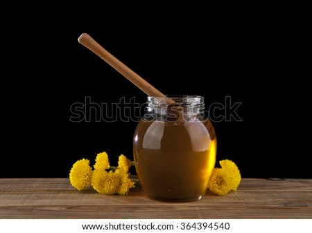 yellow flowers and honey on a black background - stock photo