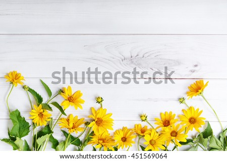Yellow flowers on light wooden background. High top view.