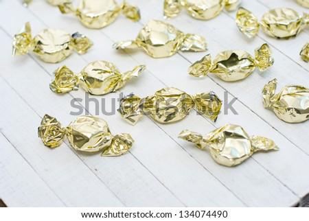 yellow foil wrapped candies on bright wooden table