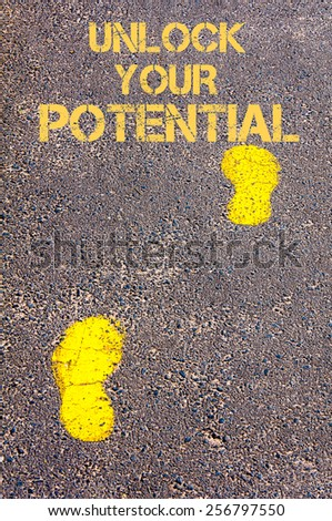Yellow footsteps on sidewalk towards Unlock your Potential message, Success conceptual image - stock photo