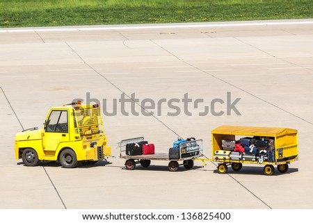 Yellow Freight trolleys with loaded baggage on the runway tarmac - stock photo