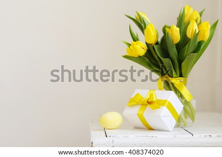 Yellow, fresh tulips in a vase on a wooden table. Gift and Easter eggs. - stock photo