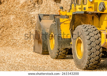 Yellow front loader with bucket down scooping wood chips for biofuel. View from left behind vehicle with pile in front of it. - stock photo