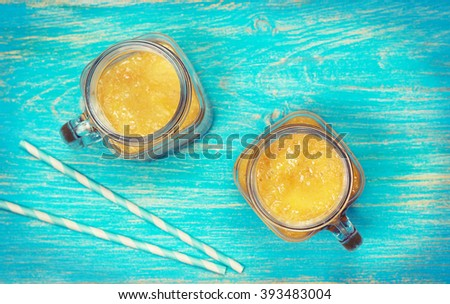 yellow fruit smoothies in mason jars on a blue wooden background (top view, toning) - stock photo