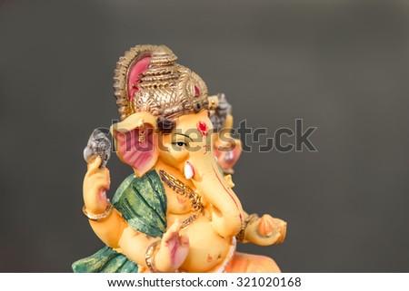 Yellow Ganesh (Ganapati- Elephant God) in Hindusim mythology closeup hold the weapons maze and axe pose focused on eye - stock photo