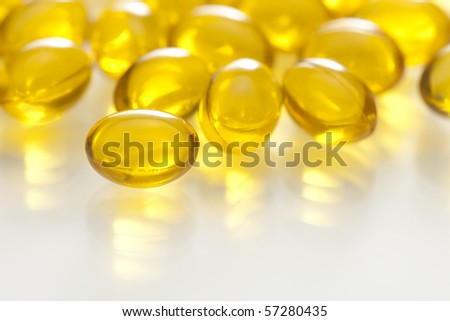 Yellow gel capsule pill on reflective white surface - stock photo
