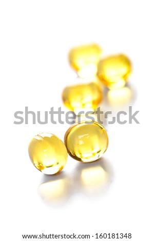 yellow gelatin pills on white background  - stock photo