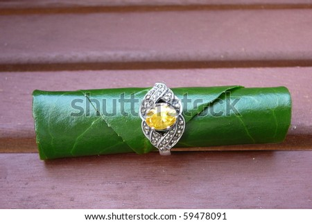 Yellow Gemstone Ring with Green Leaf - stock photo