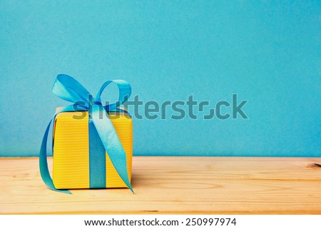 yellow gift box with ribbon on wooden background - stock photo