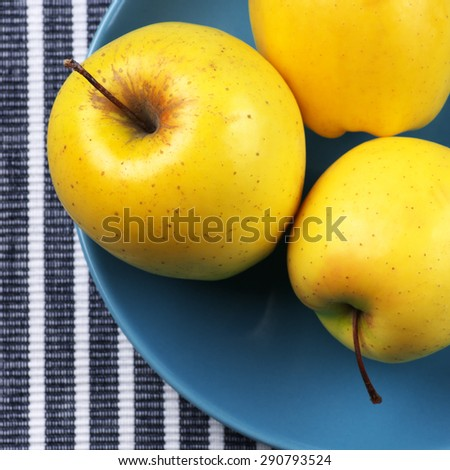 Yellow Golden Delicious apples in blue plate on striped tablecloth. Top view point. - stock photo