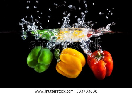 Yellow, green and red peppers dropped into water with splash isolated on black background