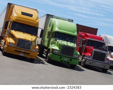 Yellow, green and red semi-trailer trucks stand side-by-side at a rest area in North America. - stock photo