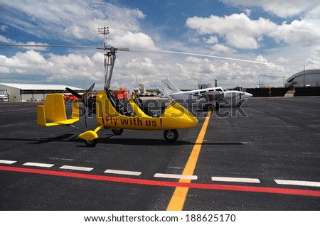 Yellow gyroplane parked on the apron in the international airport - stock photo