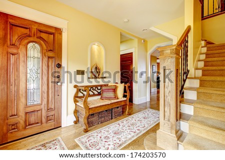 Yellow hallway with hardwood floor, stairs and rustic wood hallway storage seat - stock photo