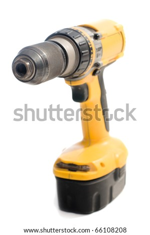 Yellow hand electric drill on battery charger