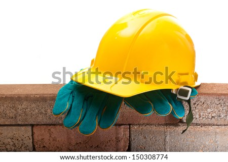 Yellow hard hat and a brick wall on a white background - stock photo