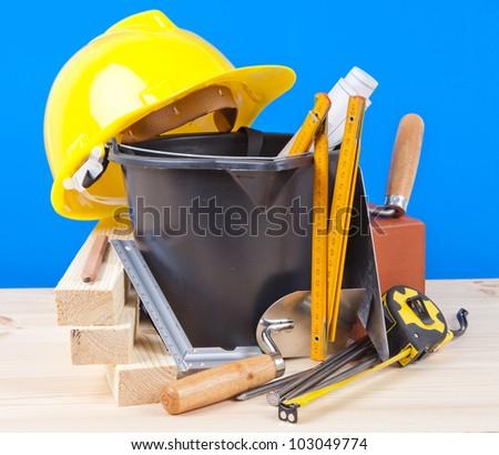 yellow hard hat and mason tools - stock photo