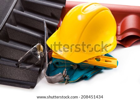 Yellow hard hat, plastic roofs, level, goggles, gloves, scrap, plumb, screws for mounting - stock photo