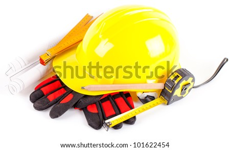 yellow hardhat, tools and construction plans on white background - stock photo