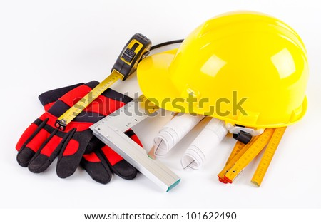 yellow hardhat, tools and construction plans on white background