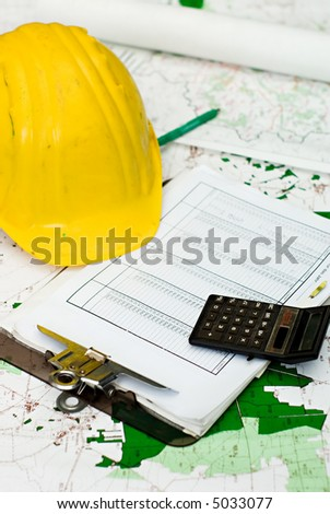 yellow hart hat, clipboard and calculator lying on maps and different plans