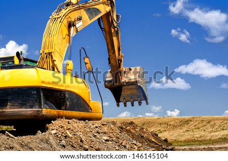 Yellow, heavy duty excavator moving soil and sand on road construction site - stock photo