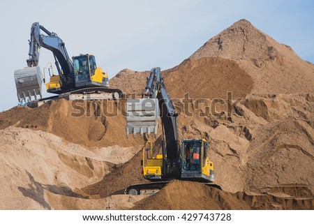 Yellow heavy excavator and bulldozer excavating sand and working during road works, unloading sand and road metal during construction of the new road - stock photo