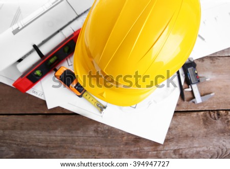 Yellow helmet and blueprint on a wooden background.