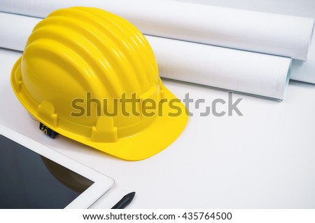 Yellow helmet and rolled paper and blueprints on white desk.