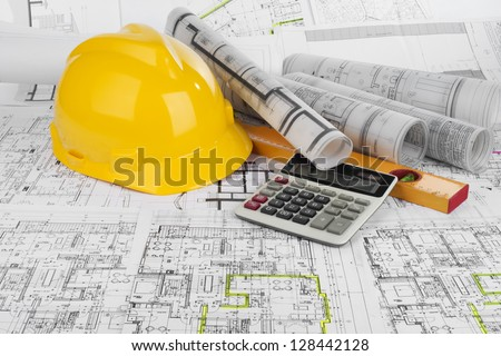 Yellow helmet, calculator, level and project drawings - stock photo
