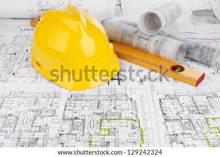 Yellow helmet, level and project drawings - stock photo