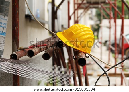 yellow helmet on tubular scaffolding, shallow DOF - stock photo