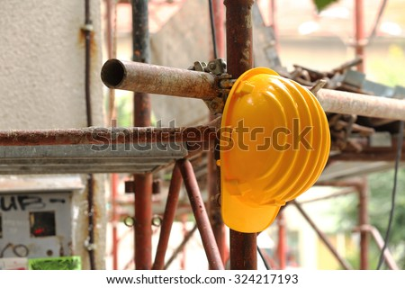 yellow helmet on tubular scaffolding, shallow DOF