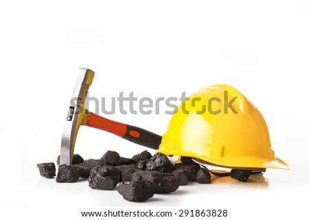 Yellow helmet with mining pickax and loose lumps of black coal