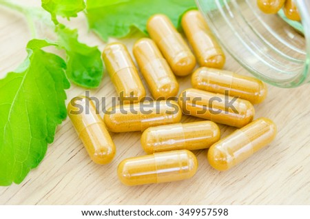 Yellow herbal capsules with green leaf on wooden background. - stock photo