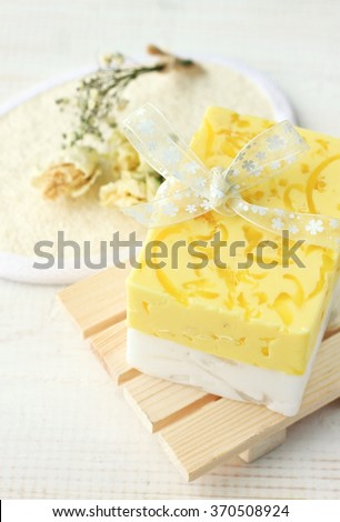 Yellow herbal soap bar. Organic skincare product, fresh handcrafted soap bar with herbs - stock photo
