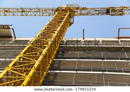 Yellow hoisting crane - stock photo