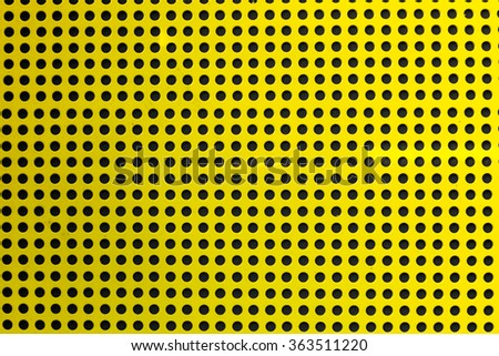 Yellow hole metal texture over a black background (selective focus, photographed with shallow DOF) - stock photo