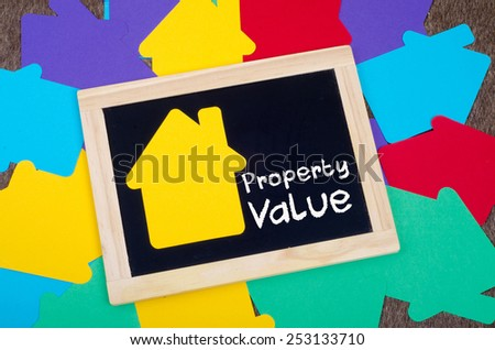 Yellow home sign on the blackboard: Real Estate Concept, Property Value - stock photo