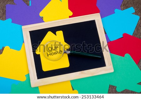 Yellow home sign with magnifying glass and blackboard: Our home text - stock photo