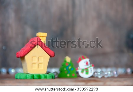 Yellow house and snowman on white bokeh background