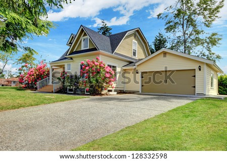Yellow house exterior with spring blooming rhododendron - stock photo
