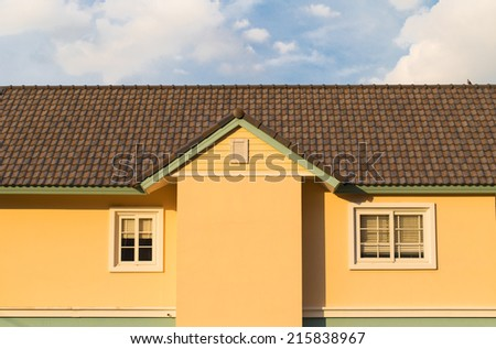 Yellow house in cloudy blue sky
