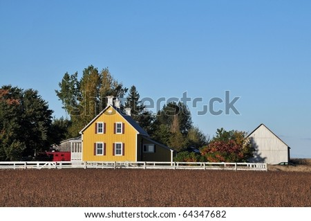 Yellow house in the soy field at fall