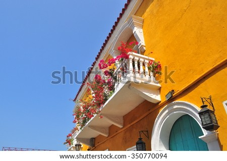 Yellow house wall with flowers at balcony, Cartagena, Colombia - stock photo