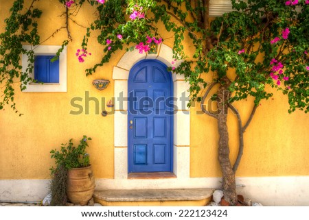 Yellow house with Blue Door in the village of Asos, Kefalonia, Greece. - stock photo