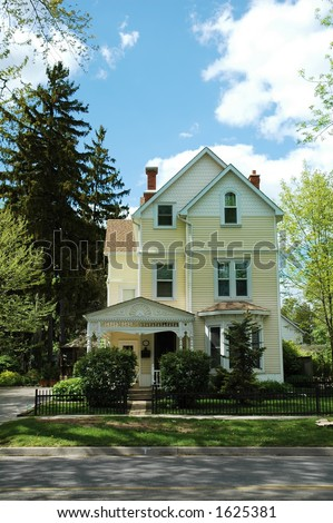 Yellow house with siding and victorian flair with bright green, manicured lawn / garden
