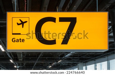 Yellow illuminated sign at airport with gate number for departing flights - stock photo